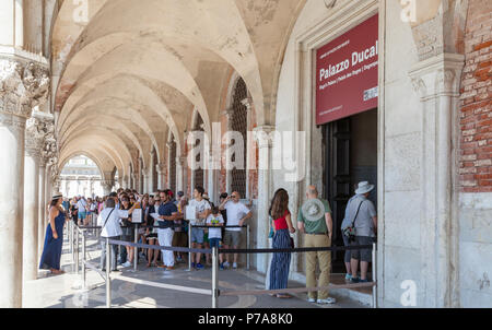 Long queue of tourists waiting to enter the Doges Palace, Palazzo Ducale, Ducal Palace in San Marco, Venice, Veneto, Italy queueing under the arcade o - Stock Photo