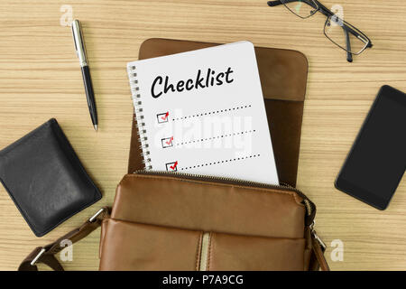 Checklist word written on notebook. Men's leather bag with personal items on wood background. To do list. - Stock Photo