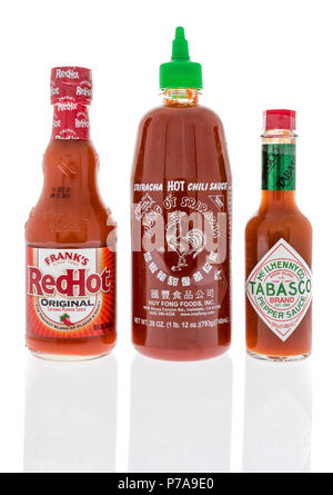 Winneconne, WI - 1 July 2018: Bottles of the best selling hot sauce in the world includes Frank's redhot, Sriracha chili sauce and Tabasco pepper sauc - Stock Photo