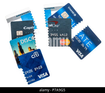 Winneconne, WI - 1 July 2018: A collection of credit cards cut up trying to get out of debt on an isolated background. - Stock Photo