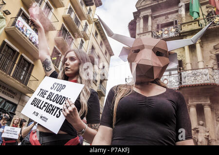 Pamplona, Navarra, Spain. 5th July, 2018. Activist against animal cruelty in bull fightings wears a paperboard bullhead mask before the San Fermin celebrations, Spain. Banner says ''stop bullfightings' Credit: Celestino Arce/ZUMA Wire/Alamy Live News - Stock Photo