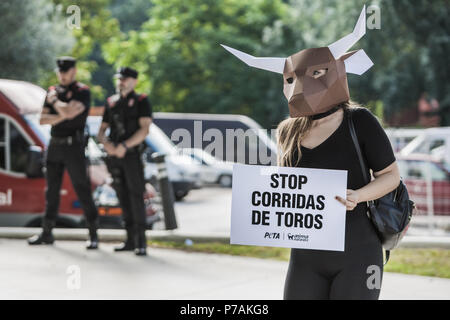 Pamplona, Navarra, Spain. 5th July, 2018. Activist against animal cruelty in bull fightings wears a paperboard bullhead mask near the local police before the San Fermin celebrations, Spain. Banner says ''stop bullfightings' Credit: Celestino Arce/ZUMA Wire/Alamy Live News - Stock Photo