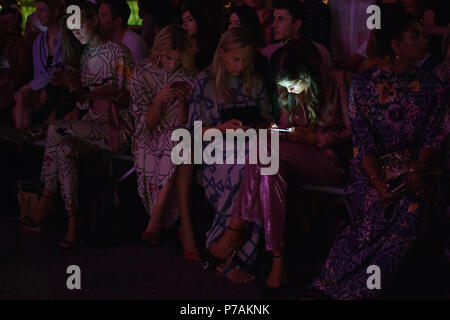 Berlin, Germany. 05th July, 2018. People sitting before the start of the fashion show. The collections for spring/summer 2019 are being presented at Berlin Fashion Week. Credit: Gregor Fischer/dpa/Alamy Live News - Stock Photo