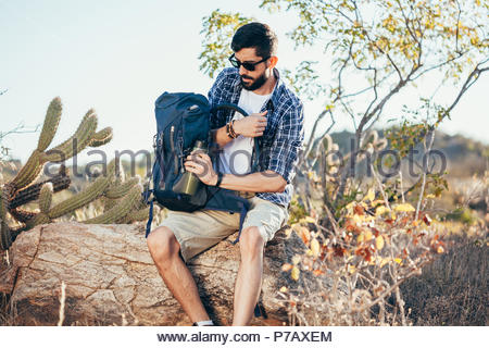 Hiker man puts water bottle in backpack. Exploring adventure hiking concept - Stock Photo