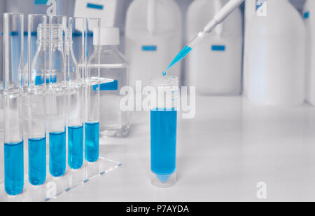 Scientific background in blue and white. Liquid sample loading with automatic pipette, space for your text - Stock Photo