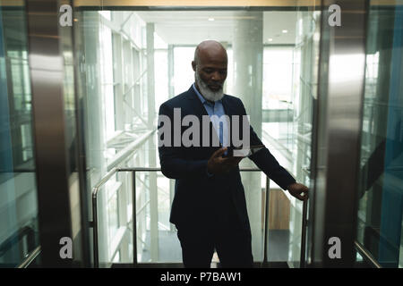 Businessman using tablet in the elevator - Stock Photo