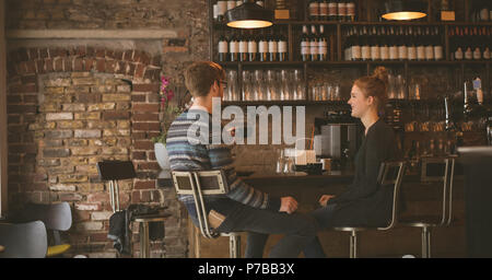 Couple having coffee while sitting at the bar counter - Stock Photo
