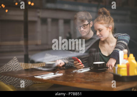 Couple using mobile phones in the cafe - Stock Photo