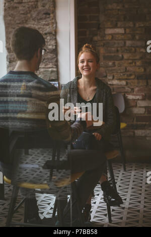 Couple chatting over coffee in the cafe - Stock Photo