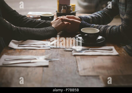 Couple holding hands in the cafe - Stock Photo