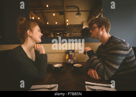 Couple talking to each other at the restaurant - Stock Photo