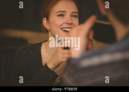 Smiling couple talking to each other at the restaurant - Stock Photo