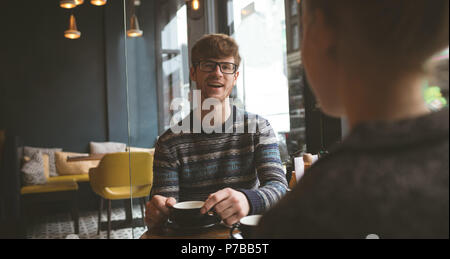 Smiling man talking to woman in cafe - Stock Photo