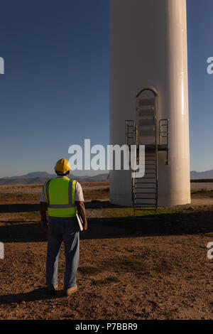 Engineer looking at a wind mill at a wind farm - Stock Photo