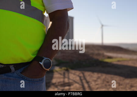 Engineer standing with hands in pocket - Stock Photo
