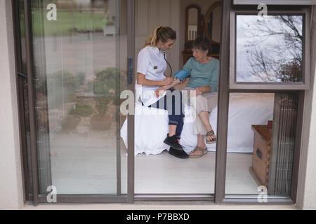 Physiotherapist checking blood pressure of senior woman - Stock Photo