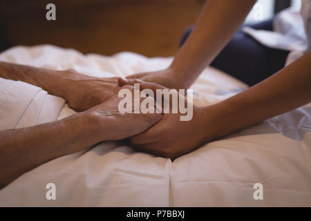 Physiotherapist holding hand of a senior woman - Stock Photo