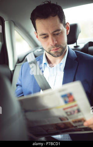 Businessman reading newspaper in a car Stock Photo