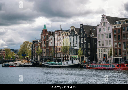 Amsterdam, Netherlands - 27 April, 2017: Houseboats and living barges in Binnenamstel canal against typical dutch houses with flag of Netherlands and  - Stock Photo