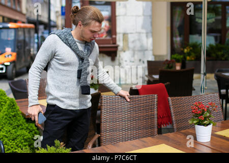 Young man standing near table at street cafe and keeping smartphone. - Stock Photo