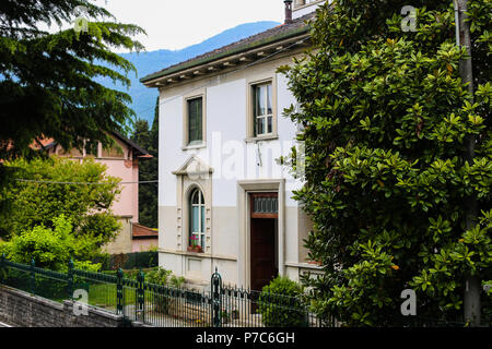 White italian house in Mandello with Alps in background. - Stock Photo