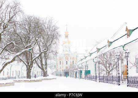 Entrance gate of the Pechersk Lavra in Kiev, Ukraine. The Gate Church of the Trinity in winter snow - Stock Photo