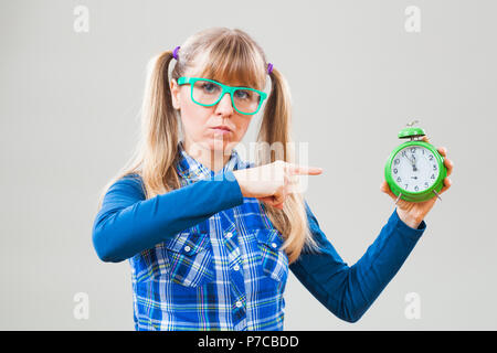 Studio shot portrait of nerdy woman who is pointing at clock that shows five to twelve time - Stock Photo