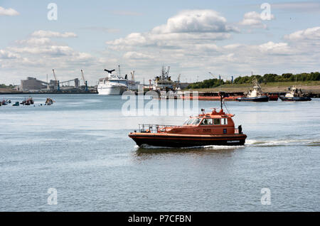 A pilot boat crosses the River Tyne, with a ship docked at the Ferry Port in the background, North Shields, Tyneside, UK - Stock Photo