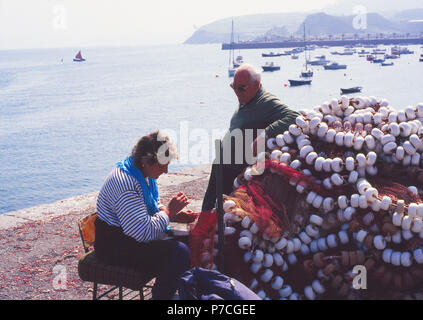 Woman sewing fishing nets at the harbour. Castro Urdiales, Cantabria, Spain.