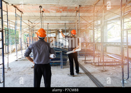 Engineer discussing with foreman about project in building construction site - Stock Photo