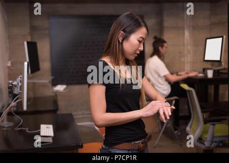 Female executive using smartwatch - Stock Photo