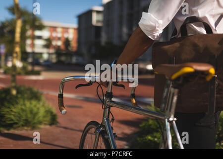 Businessman walking with his bicycle at office premises - Stock Photo