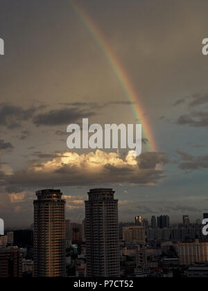 Bangkok skyline at dusk with rainbow - Stock Photo