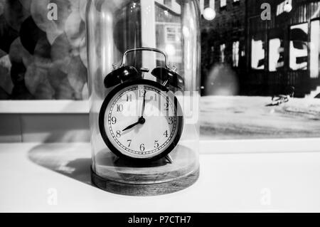 Retro alarm clock showing 8 O'clock on blurred background in black and white - Stock Photo