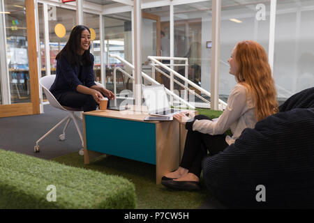Female executives interacting with each other in office - Stock Photo
