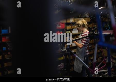 Female mechanic working in workshop - Stock Photo