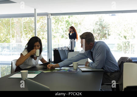 Business colleagues discussing over documents - Stock Photo
