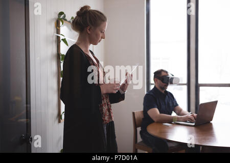 Business colleagues using glass digital tablet and laptop - Stock Photo