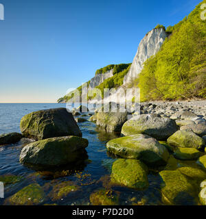 Chalk rocks and boulders on the Baltic Sea in spring, in front the Königsstuhl, behind the Victoria view, fresh green - Stock Photo