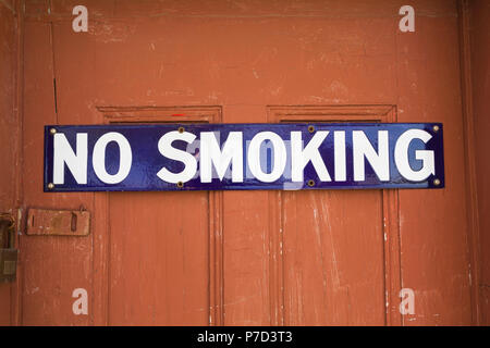 White and blue No Smoking sign on reddish brown wooden entrance door, background image - Stock Photo