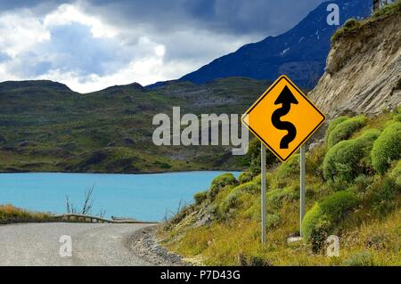 Road Sign Attention curves at Lago Pehoe, Torres del Paine National Park, Última Esperanza Province, Chile - Stock Photo
