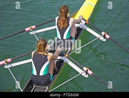 Two young women rowing race in lake - Stock Photo