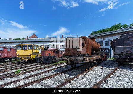 Various locomotives and a rusty hull of a steam locomotive in front of a roundhouse, Bavarian Railway Museum Nördlingen - Stock Photo
