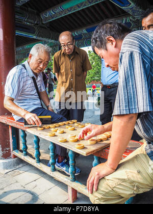 Beijing, China - September 2017: Older men playing traditional Chinese chess in the long corridor of the Temple of Heaven - Stock Photo