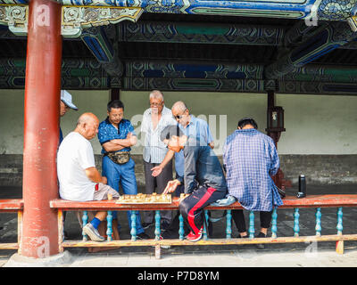 Group of men playing traditional Chinese chess in the long corridor of the Temple of Heaven, Beijing, China - Stock Photo