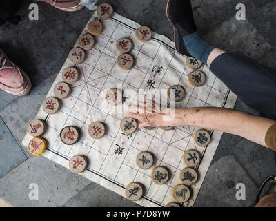 Two older men playing traditional Chinese chess on the floor in the Temple of Hevean, Beijing, China - Stock Photo