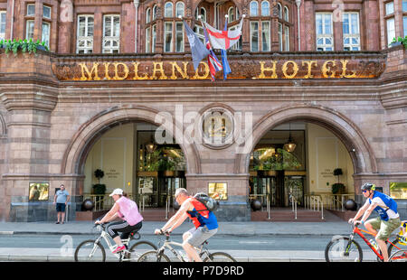 Cyclists passing the front of the Midland Hotel in Manchester, UK - Stock Photo
