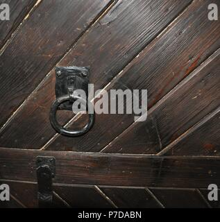 Old iron handle on an vintage brown wood door, close up - Stock Photo