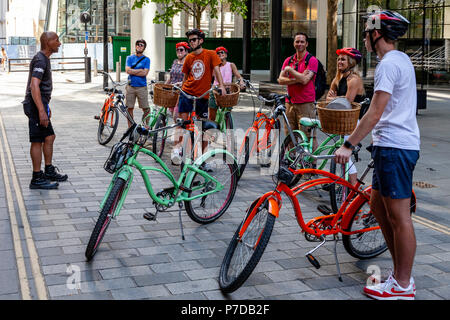 Tourists Stop In 'The City' During A Bicycle Tour Of London Sights, London, United Kingdom - Stock Photo