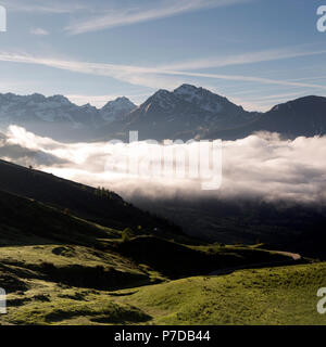 mountainscape near col de vars in french provence alps on early summer morning with clouds raising in valley - Stock Photo